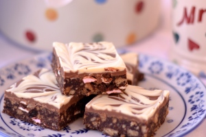 Classic Chocolate Tiffin - Crushed biscuit, sultanas and marshmallows mixed with a gooey chocolatey syrup mixture, then smothered in milk and white chocolate. Absolutely gorgeous! | thehecticcook.com